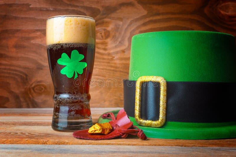 Concepto de StPatrick con el sombrero, la cerveza y el oro verdes del duende foto de archivo libre de regalías