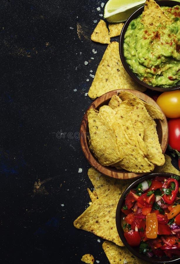 Concepto de Tex-Mex, Nachos, Guacamole, salsa de la salsa, Backgroun negro foto de archivo libre de regalías