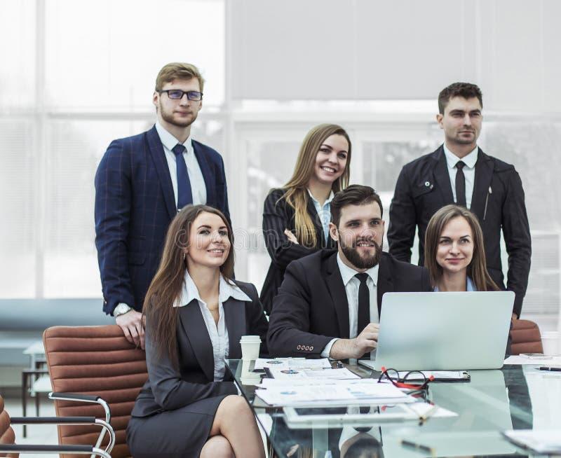 Concepto de trabajo en equipo - un equipo acertado del negocio en el lugar de trabajo en la oficina foto de archivo