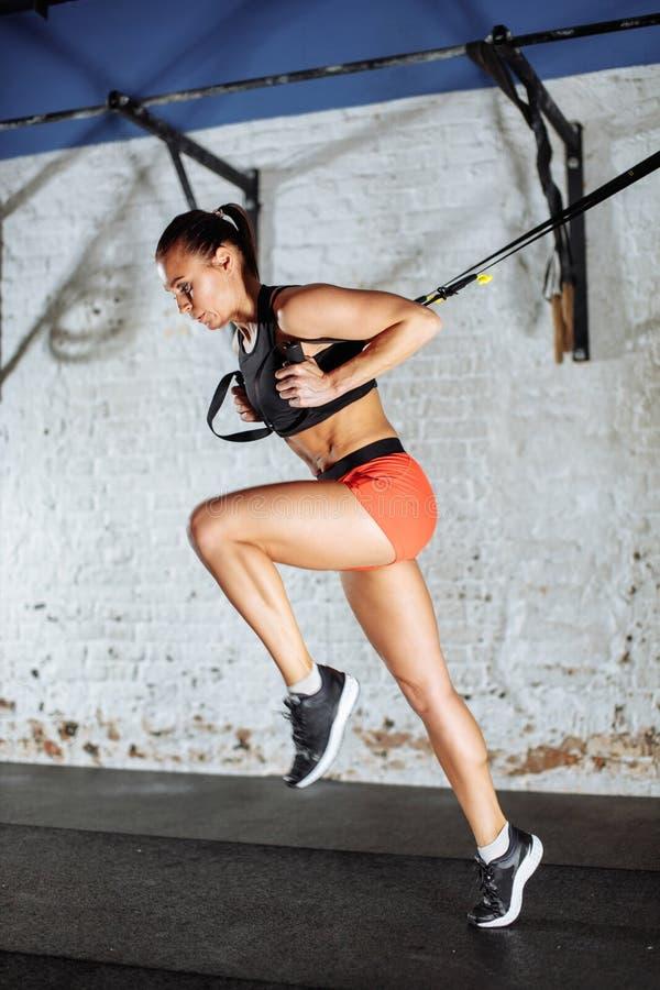 Concepto de Trx señora que ejercita sus músculos con la ayuda de la honda del instructor de la suspensión fotos de archivo