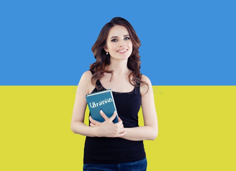Concepto de Ucrania Mujer morena sonriente bonita contra el fondo ucraniano de la bandera Recorrido en Ucrania fotografía de archivo