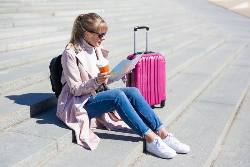 Concepto de vacaciones, turismo y viajes - mujer joven con mapa turístico y maleta imagen de archivo