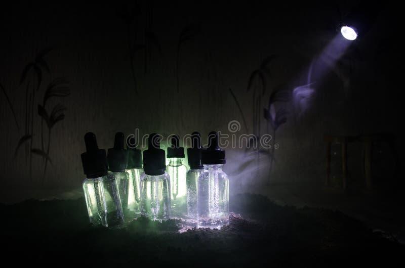 Concepto de Vape Nubes de humo y botellas líquidas del vape en fondo oscuro Efectos luminosos Útil como anuncio del fondo o del v fotos de archivo libres de regalías