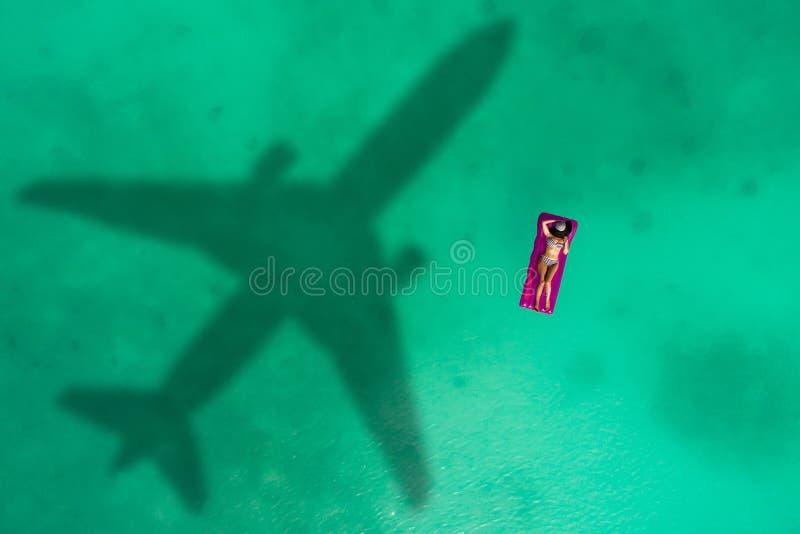 Concepto de viaje en avión a un destino exótico con la sombra de un avión comercial volando sobre una hermosa playa tropical. P imagenes de archivo