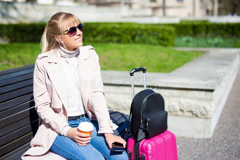Concepto de viajes de verano y vacaciones - joven sentada con maleta en el parque y disfrutando del verano imágenes de archivo libres de regalías
