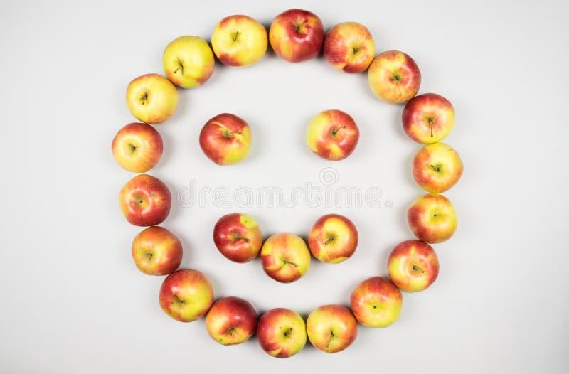 Concepto de vida feliz y sana como manzanas frescas rojas y amarillas que forman la cara sonriente en el fondo blanco fotografía de archivo