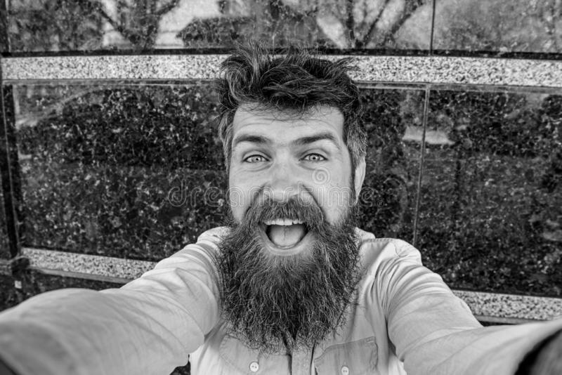 Concepto de Vlogging Hombre, turista con la barba y bigote en la cara alegre, sonriente, fondo de mármol negro Inconformista fotos de archivo libres de regalías