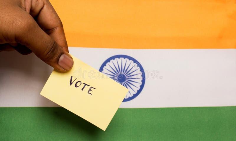 Concepto de votación - etiqueta engomada de votación escrita mano de la tenencia de la persona en la bandera de la India imagenes de archivo