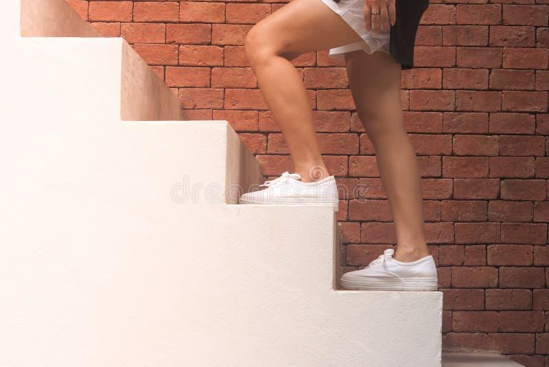 Concepto del éxito empresarial: La mujer está caminando encima de las escaleras concretas blancas afuera en los edificios con el  fotos de archivo libres de regalías