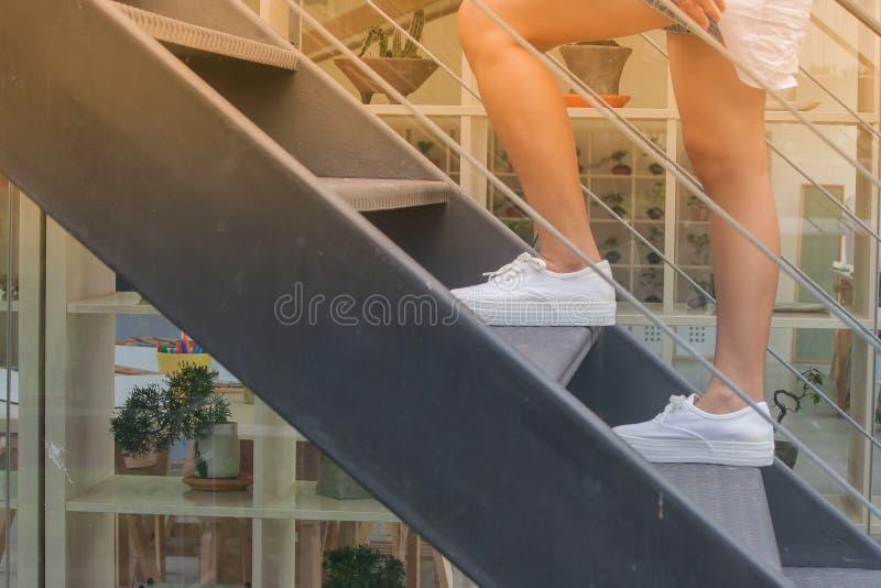 Concepto del éxito empresarial: La mujer está caminando encima de las escaleras negras del metal fuera de los edificios fotografía de archivo libre de regalías