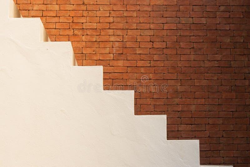 Concepto del éxito empresarial: Vista lateral de las escaleras vacías blancas con el fondo marrón de la pared de ladrillo foto de archivo