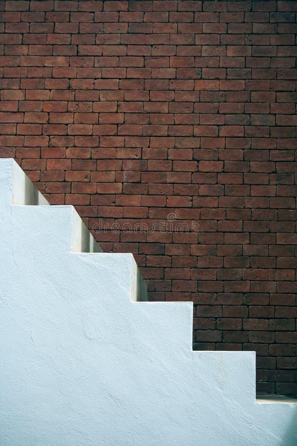 Concepto del éxito empresarial: Vista lateral de las escaleras vacías blancas con el fondo marrón de la pared de ladrillo foto de archivo libre de regalías