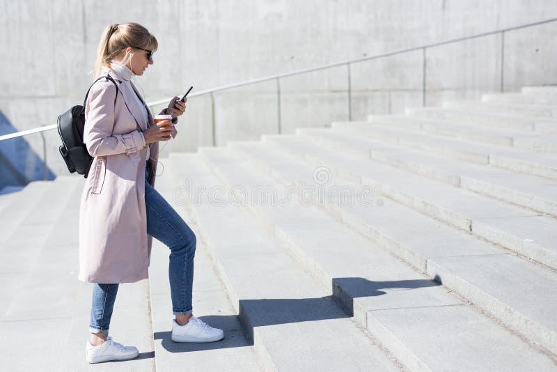 Concepto del éxito y de la carrera - vista lateral de la mujer joven que camina encima de las escaleras fotos de archivo