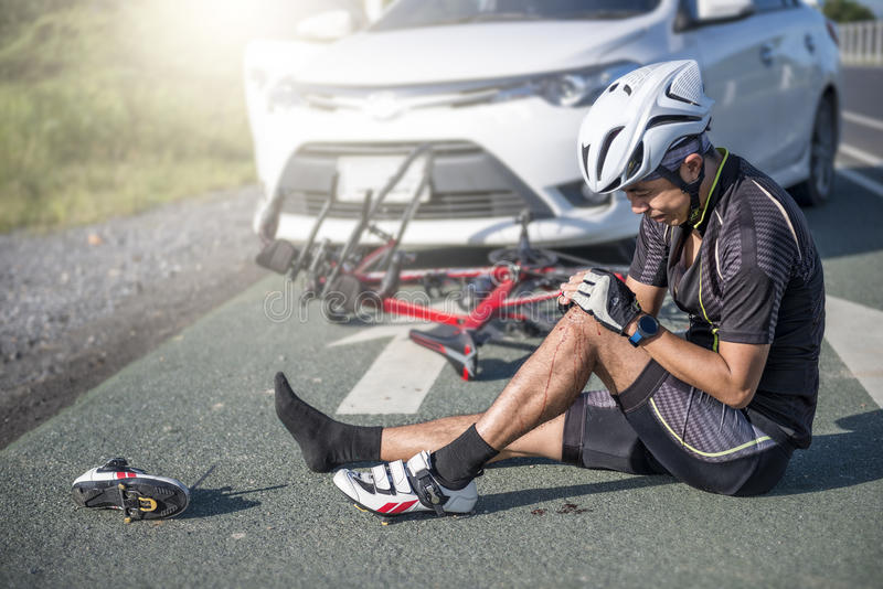Concepto del accidente, ciclista masculino inconsciente que miente en el camino fotos de archivo