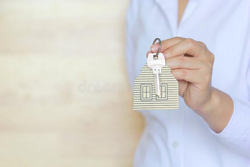 Concepto del agente inmobiliario, llave de la tenencia de la mano de la mujer con un llavero en la forma de la casa imágenes de archivo libres de regalías