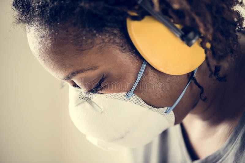 Concepto del ambiente del trabajo de la seguridad de la protección auditiva de la mujer que lleva negra foto de archivo libre de regalías