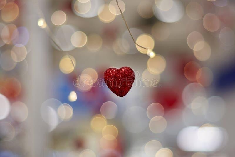 Concepto del amor, símbolo en forma de corazón del amor que cuelga en el aire en fondo del bokeh de la guirnalda foto de archivo