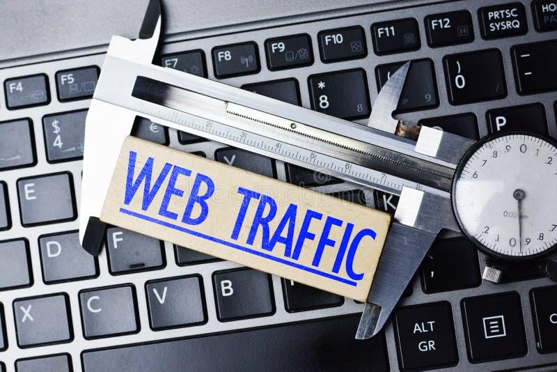 Concepto del analytics del web, con el calibrador en el teclado del ordenador portátil que mide tráfico en línea del sitio web foto de archivo libre de regalías