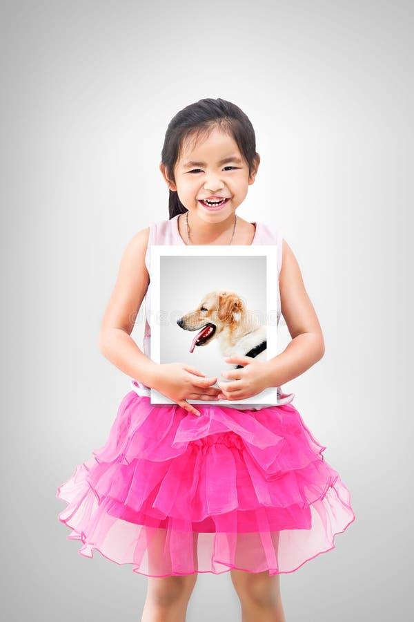 Concepto del animal doméstico del amor niña que lleva a cabo una imagen de su perro imagenes de archivo