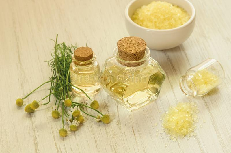 Concepto del Aromatherapy o del BALNEARIO Tinte amarillo o aceite del agua de la manzanilla, flor y sal de baño en fondo blanco d fotos de archivo