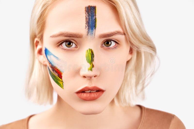 Concepto del arte de la cara El tiro ascendente cercano de la hembra hermosa con mirada atractiva, tiene maquillaje art?stico baj imagen de archivo libre de regalías