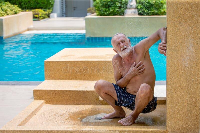 Concepto del ataque del coraz?n Sufrimiento del hombre mayor del dolor de pecho en ducha de lluvia al aire libre por la piscina imagen de archivo libre de regalías