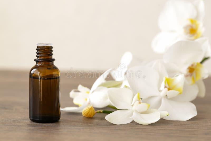 Concepto del balneario con las orquídeas y la botella blancas del aceite esencial, espacio para el texto Aceite del masaje Flor d fotos de archivo