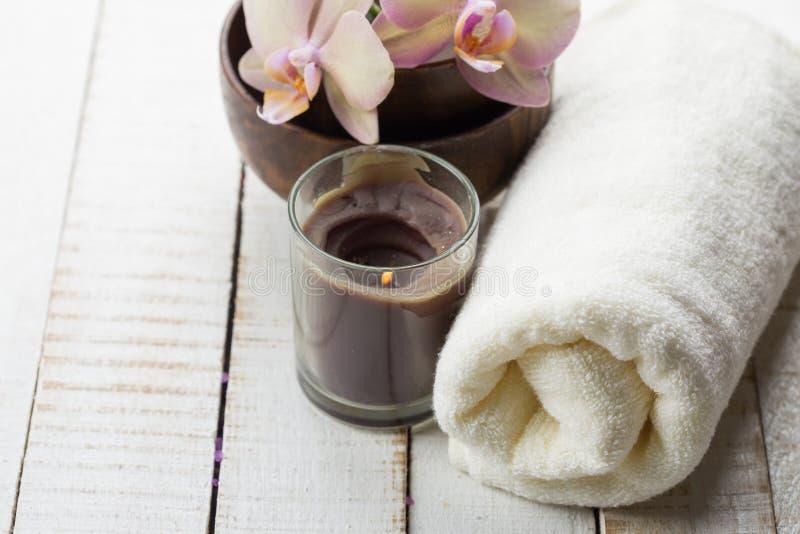 Concepto del balneario Toalla de baño, flores frescas en el backgroun de madera blanco foto de archivo libre de regalías