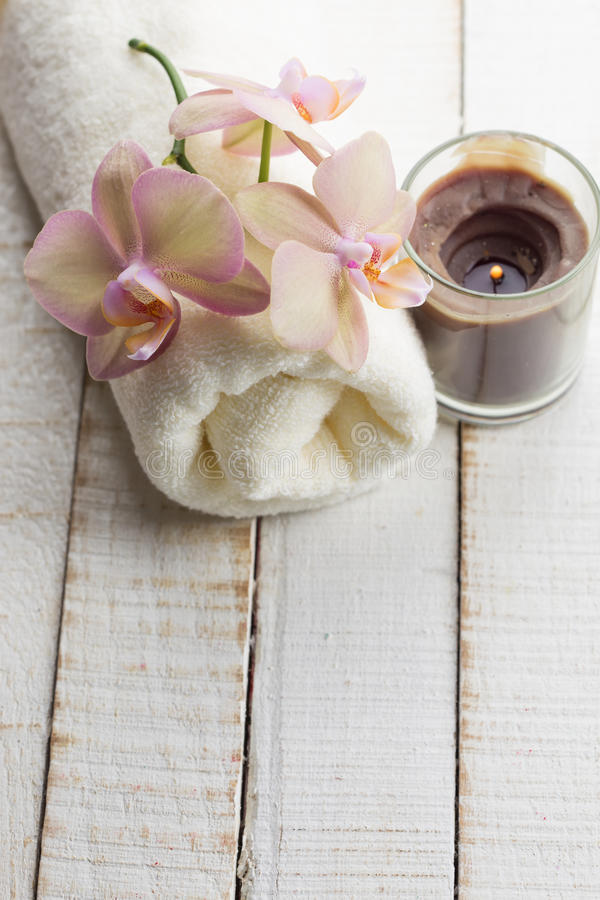 Concepto del balneario Toalla de baño, flores frescas en el backgroun de madera blanco imágenes de archivo libres de regalías