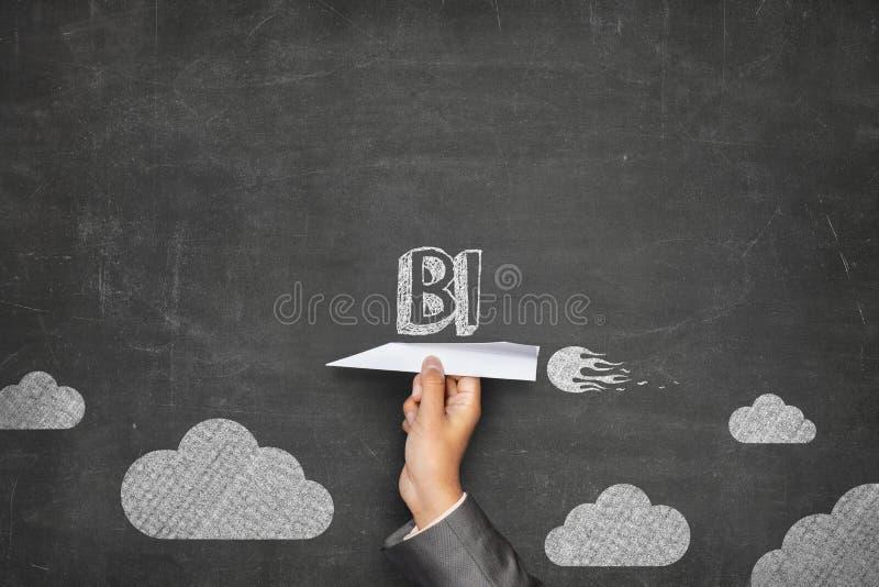 Concepto del BI en la pizarra con el avión de papel fotos de archivo