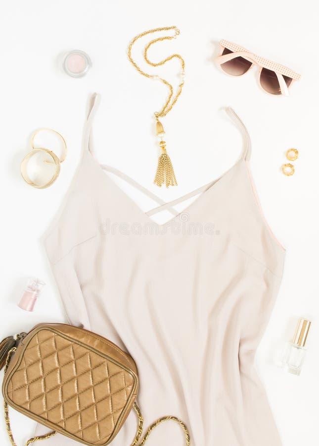 Concepto del blog de la belleza Equipo de la mujer Vestido rosado, gafas de sol rosadas, bolso del oro, pulseras, collar, pendien foto de archivo libre de regalías