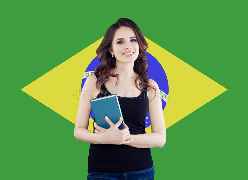 Concepto del Brasil con el estudiante de mujer lindo contra el fondo brasileño de la bandera Viaje en el Brasil y aprender lengua imagen de archivo