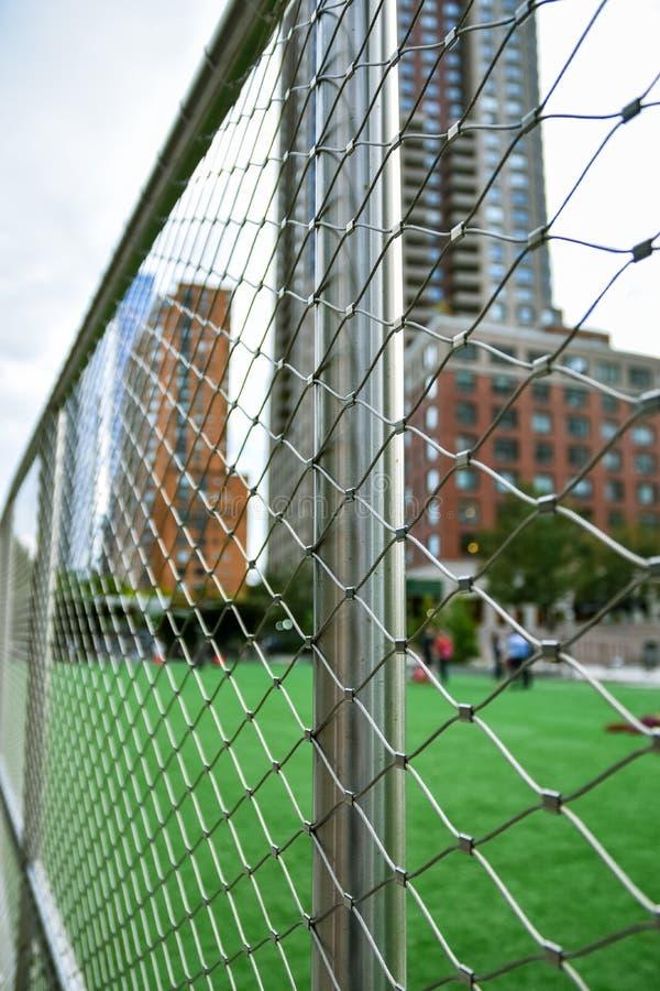 Concepto del campo de fútbol desenfocado en la ciudad de NYC , Manhattan, entre los rascacielos La cerca en el primero plano se e fotografía de archivo libre de regalías