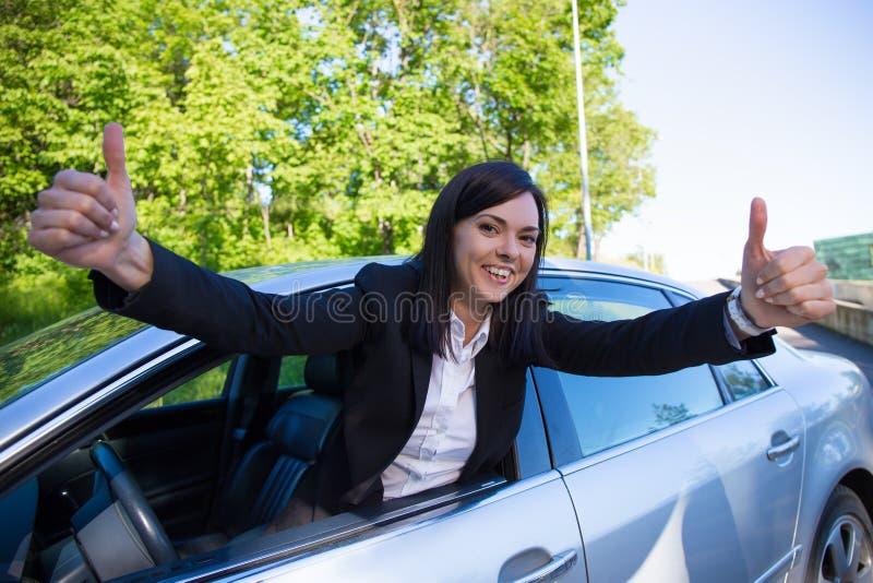 Concepto del carné de conducir - mujer feliz con el coche imagenes de archivo