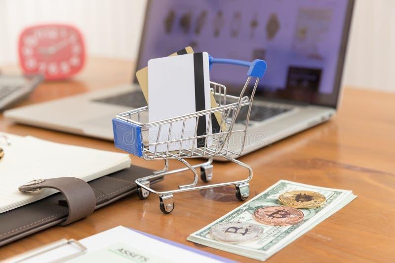Concepto del comercio electrónico, mano que sostiene el dinero y la tarjeta de crédito en carro de la compra con el fondo abierto fotos de archivo libres de regalías