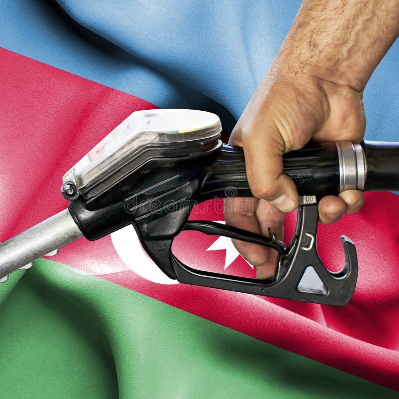 Concepto del consumo de la gasolina - manguera de la tenencia de la mano contra la bandera de Azerbaijan fotos de archivo