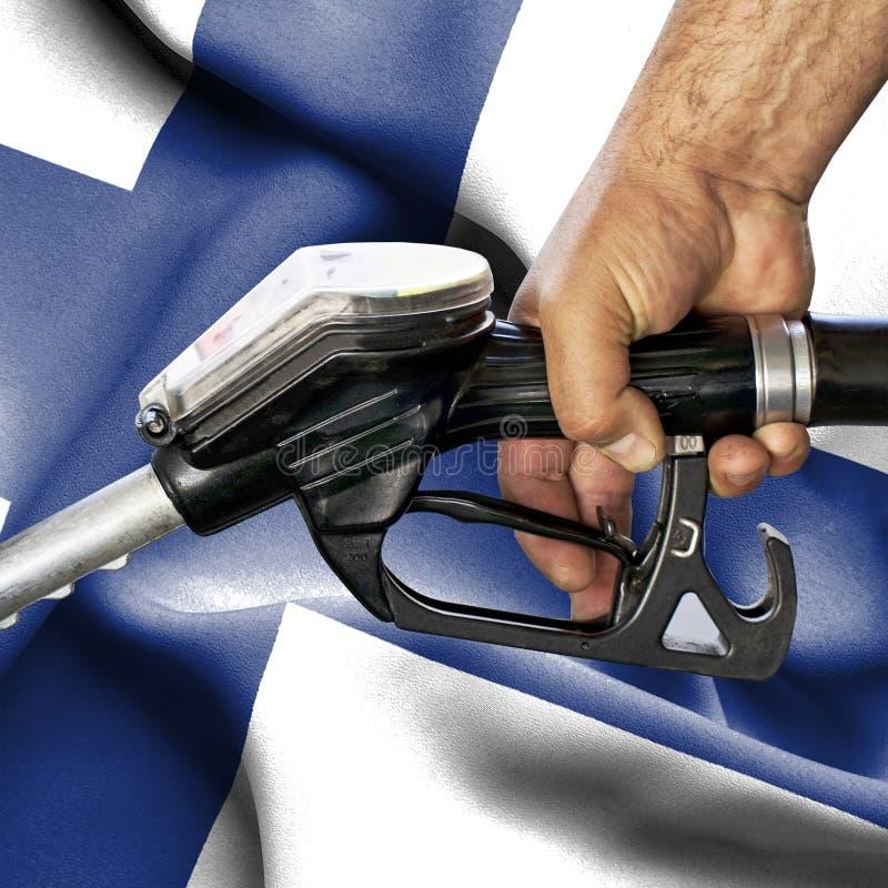 Concepto del consumo de la gasolina - manguera de la tenencia de la mano contra la bandera de Finlandia imagen de archivo libre de regalías