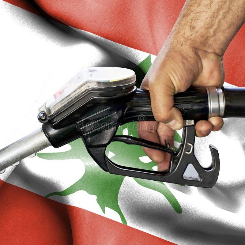 Concepto del consumo de la gasolina - manguera de la tenencia de la mano contra la bandera de Líbano foto de archivo libre de regalías