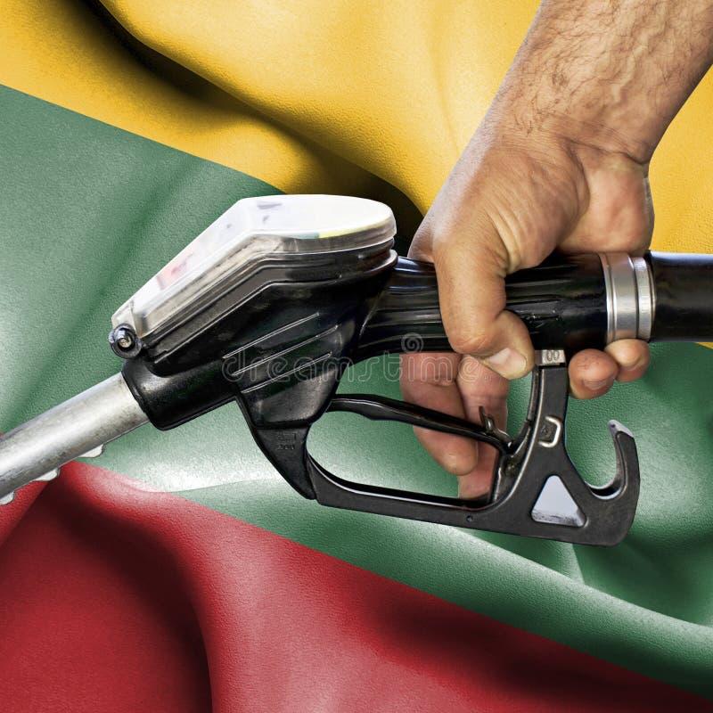 Concepto del consumo de la gasolina - manguera de la tenencia de la mano contra la bandera de Lituania fotografía de archivo
