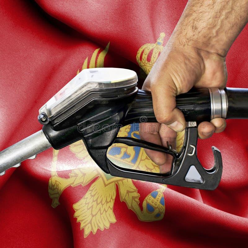 Concepto del consumo de la gasolina - manguera de la tenencia de la mano contra la bandera de Montenegro foto de archivo