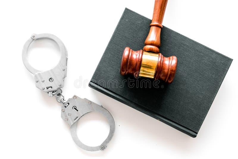 Concepto del crimen Esposas del metal cerca del mazo del juez y del libro de ley en la opinión superior del fondo blanco imágenes de archivo libres de regalías