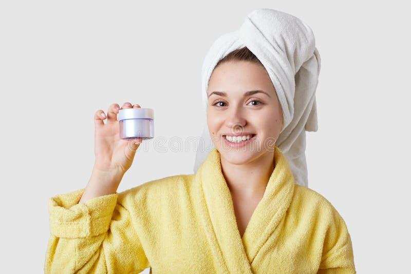 Concepto del cuidado de piel La mujer caucásica hermosa que va a aplicar la crema hidratante en la cara, vestida en albornoz y to foto de archivo libre de regalías