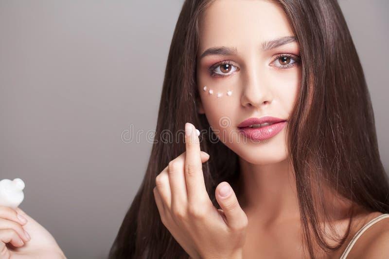 Concepto del cuidado de piel Mujer hermosa con la crema de la mano, loción encendido él imagen de archivo