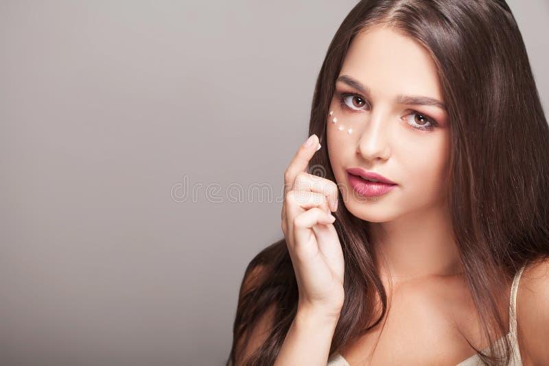 Concepto del cuidado de piel Mujer hermosa con la crema de la mano, loción encendido él fotos de archivo libres de regalías