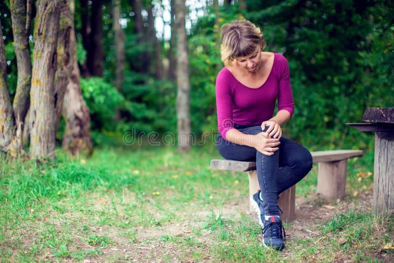 Concepto del cuidado médico Mujer que sufre de dolor en la rodilla al aire libre fotografía de archivo libre de regalías