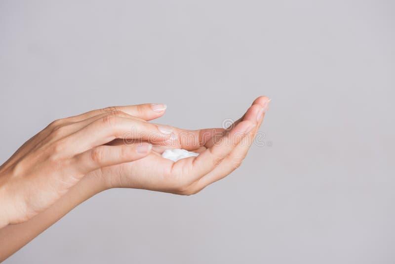 Concepto del cuidado médico Primer tirado de las manos de la mujer joven que aplican la crema hidratante de la mano imagenes de archivo
