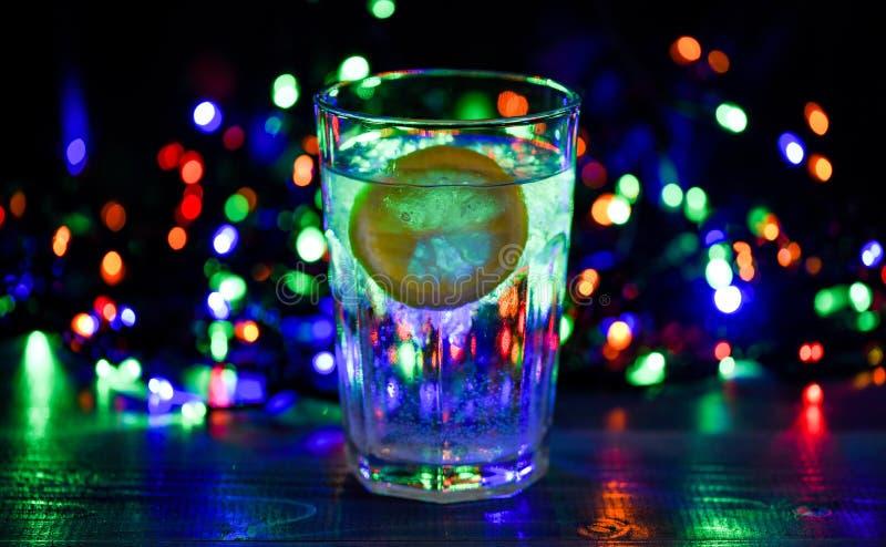 Concepto del cuidado médico Qué a beber en la fiesta de Navidad Vidrio de cóctel con agua y la rebanada de guirnalda defocused de imagenes de archivo