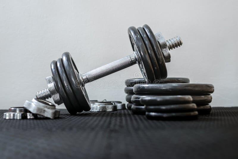 Concepto del cuidado m?dico Pesas de gimnasia o pesos del hierro en piso negro en el gimnasio Equipo de entrenamiento del peso fotos de archivo