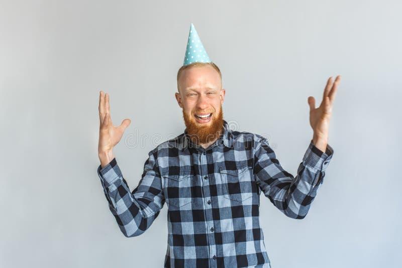 Concepto del cumpleaños Hombre maduro en la situación del casquillo aislado en las manos grises encima de la risa alegre foto de archivo