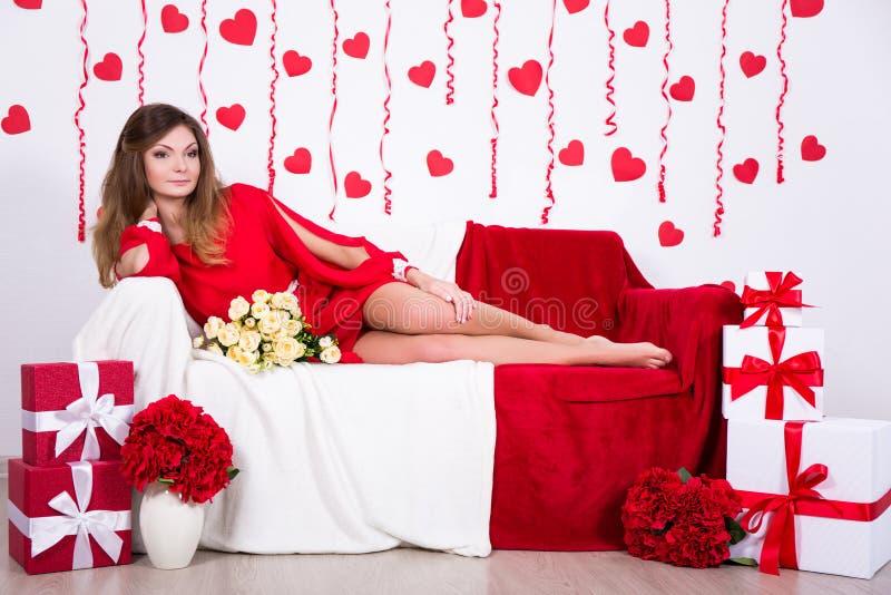 Concepto del cumpleaños - mujer magnífica en el vestido rojo largo que se sienta en d imágenes de archivo libres de regalías